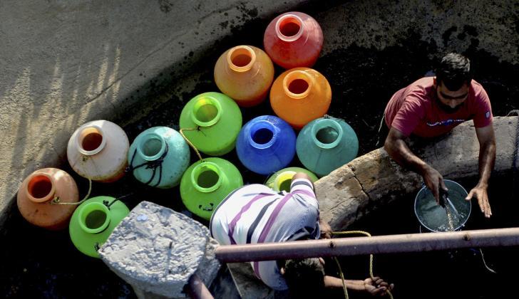 Las personas sacan con poleas agua de los pozos para así llenar los bidones.