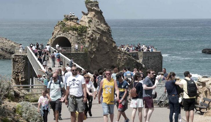 """La gente camina frente al """"Rocher de La Vierge"""" en Biarritz, Francia."""