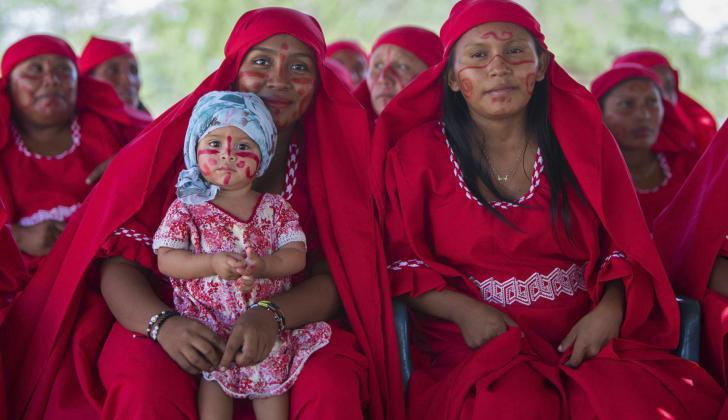 Mujeres de la comunidad Kepischon, en Uribia, cargan a una bebé durante una jornada de la Unicef y el Bienestar Familiar.