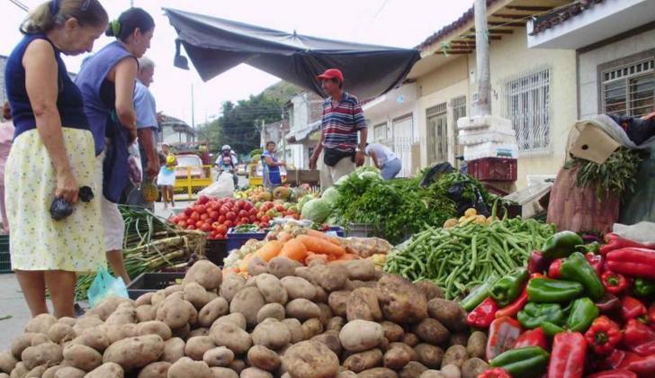 Personas compran frutas y verduras en el mercado.