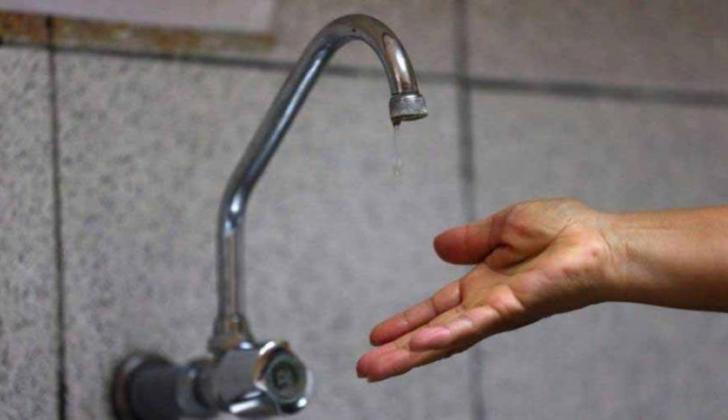 Una persona acerca su mano al grifo para verificar que haya agua.