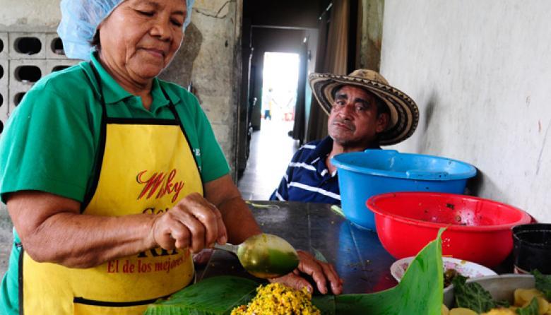 Raquel De la Asunción, una de las organizadoras del Festival del Pastel, arma uno de los envueltos mientras su esposo Julián De la Hoz la observa. El hombre tenía la misión ayer de amarrar e identificar cada uno de los pasteles.