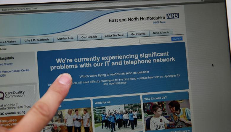 Una mujer señala el sitio web del NHS en el que se notifica a sus usuarios de problemas en su red tras el ciberataque del viernes.