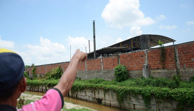 Un habitante del barrio Colombia señala hacia las chimeneas de la caldera del matadero Santa Cruz en Malambo de donde provienen malos olores.