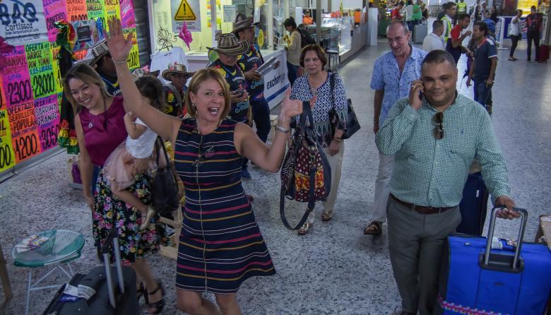 La barranquillera Lorna López baila con un grupo de millo al llegar al aeropuerto Ernesto Cortissoz.