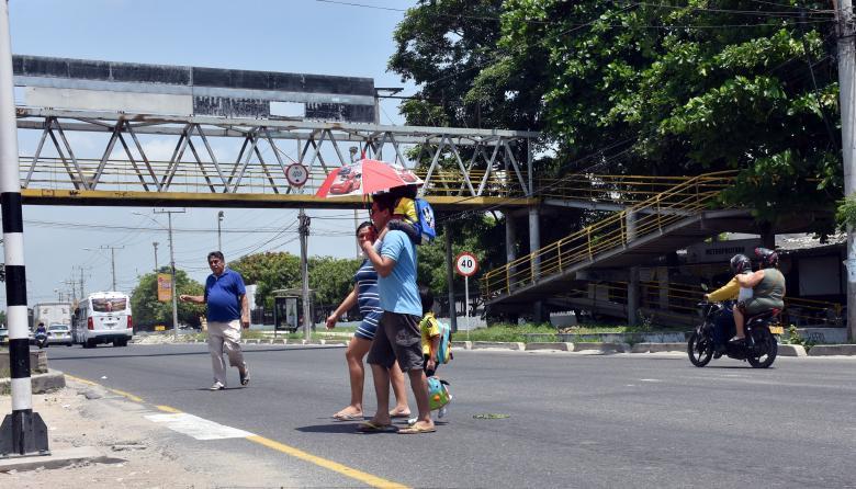 Peatones cruzan la Avenida Circunvalar, puesto que el puente está inconcluso.