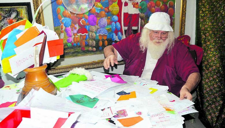 Hernando Grisales revisa las cartas que recibió este año de los niños.