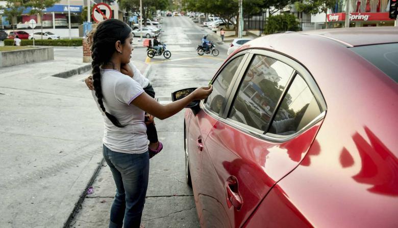 Una mamá con su hija en brazos se acerca a ofrecer dulces a conductores que se detienen en un semáforo.