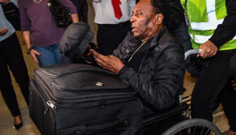 Pelé saliendo en silla de ruedas de la clínica en París.