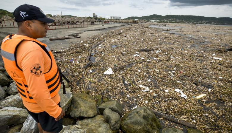 Un socorrista observa con tristeza la gran cantidad de residuos en el sector de Ponimar en Puerto Colombia.