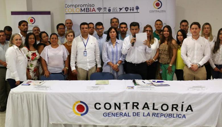 Luis Carlos Pineda, contralor delegado, durante la firma del acta de compromiso con participantes en mesa.