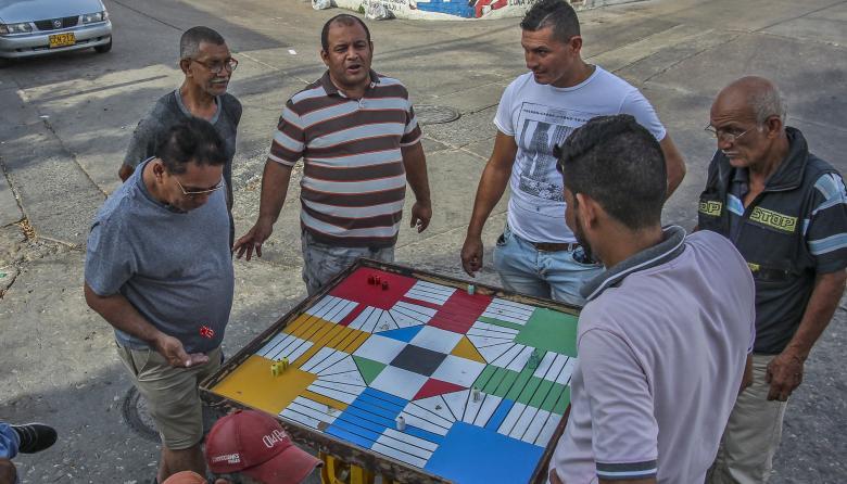 Varios residentes de Barrio Abajo se reúnen en torno a un partido de parqués, en una de las tradicionales esquinas de este sector.