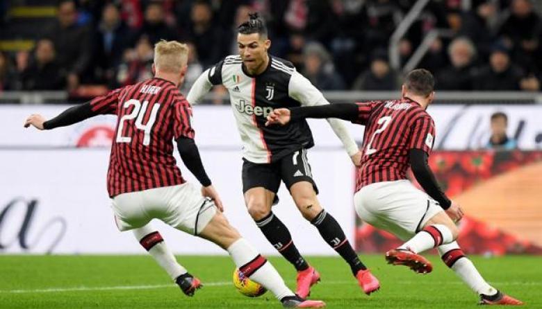 Cristiano Ronaldo protege el balón ante la marca de dos jugadores del Milan.