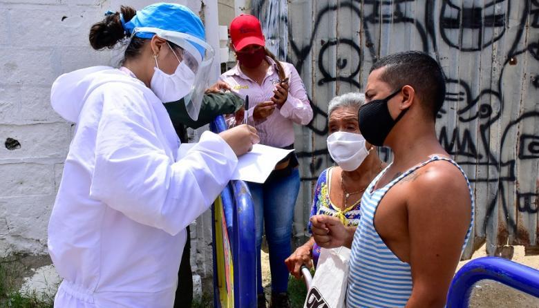 Una trabajadora de la salud toma los datos de dos residentes en la zona.