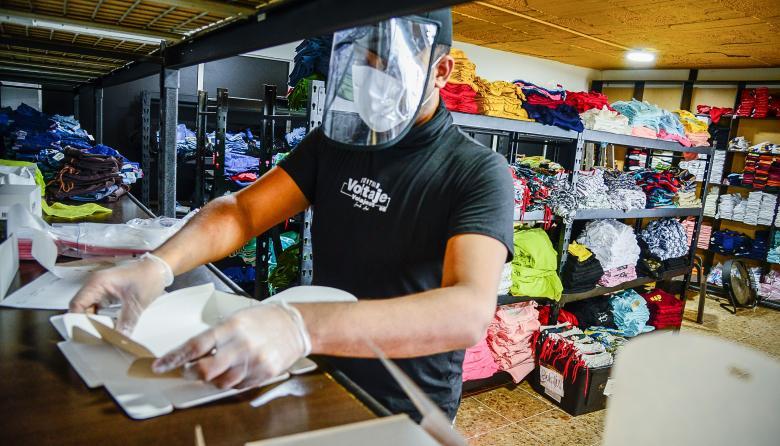 Un empleado de un taller portando guantes y elementos protectores faciales.