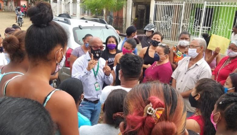 Édgar Arrieta, enlace de la Alcaldía, explica a los habitantes del barrio La Candelaria sobre el falso funcionario.