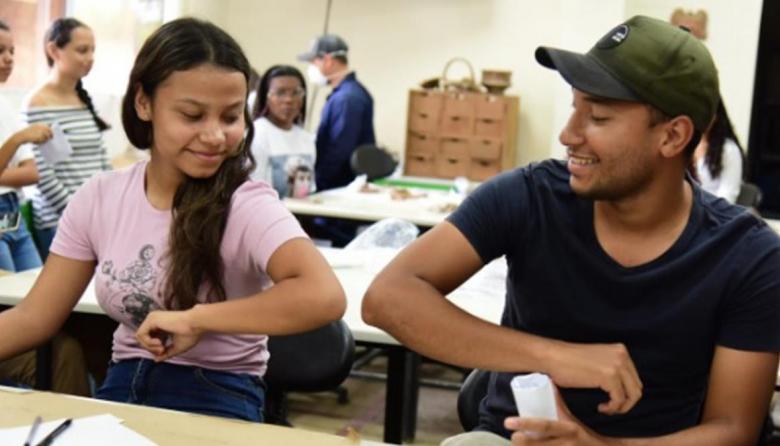 Dos estudiantes de la Universidad del Magdalena se saludan 'codo con codo' para prevenir el Covid-19.