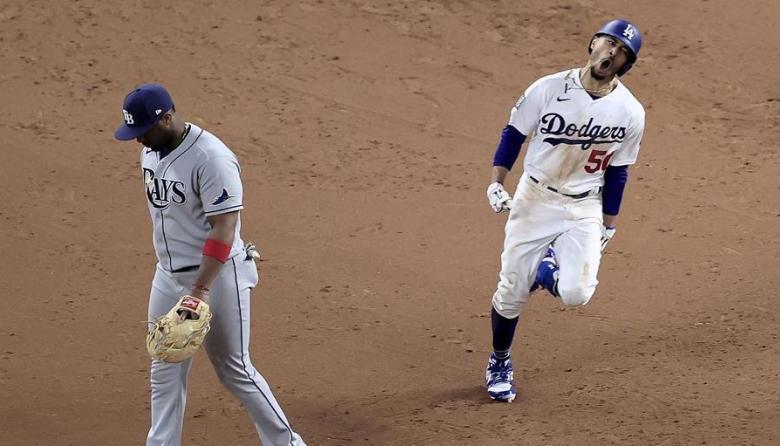 Mookie Betts celebra al pasar cerca del primera base de Rays, Yandy Diaz, tras conectar un cuadrangular.