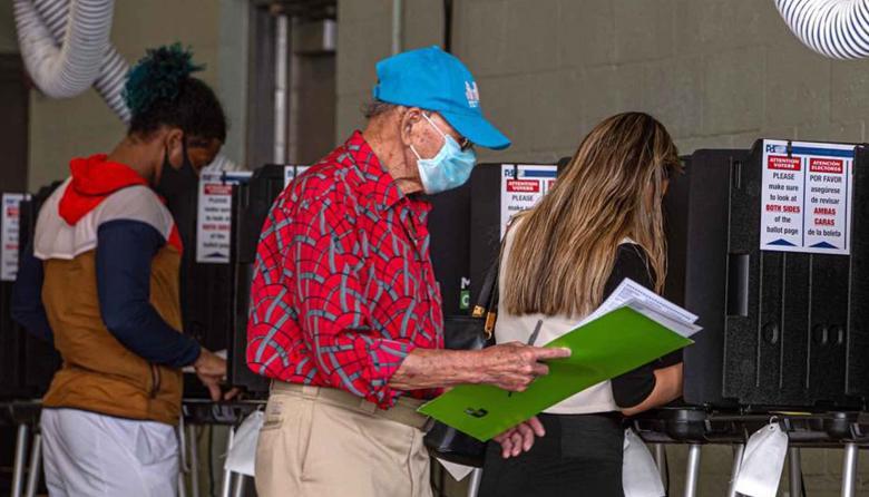 Personas llenan sus papeletas de votación este martes en el centro de votación en Miami Beach, Florida.