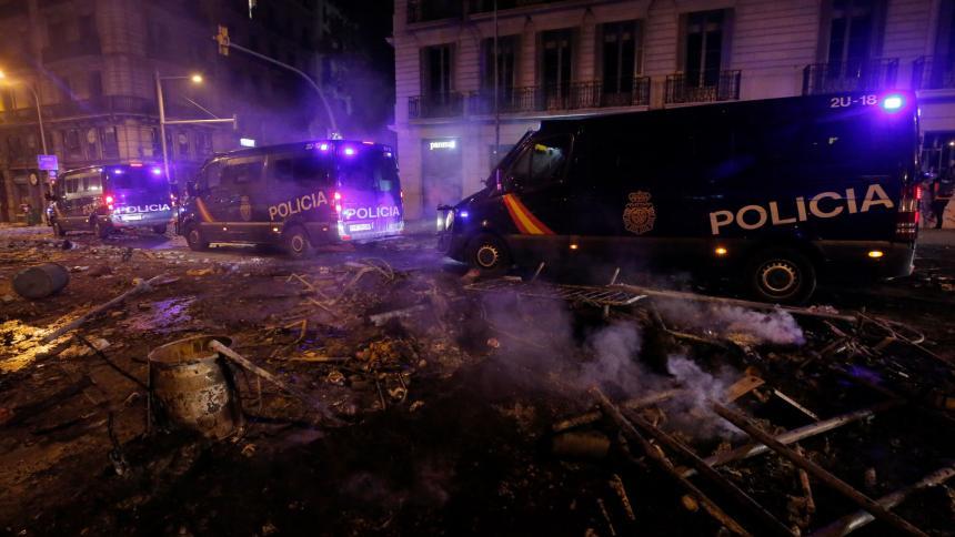 Las furgonetas de la policía conducen sobre escombros en Barcelona, después de que la violencia se intensificó durante los enfrentamientos, con separatistas radicales lanzando proyectiles a la policía, que respondieron con gases lacrimógenos y balas de goma que provocaron escenas de caos en el centro de la ciudad.