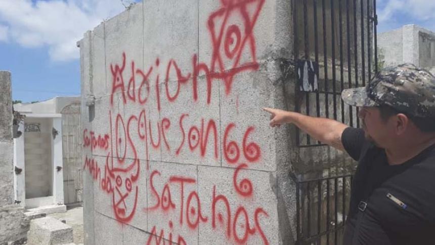Alexis Salcedo, uno de los sepultureros, enseña los mensajes que han aparecido en el cementerio.
