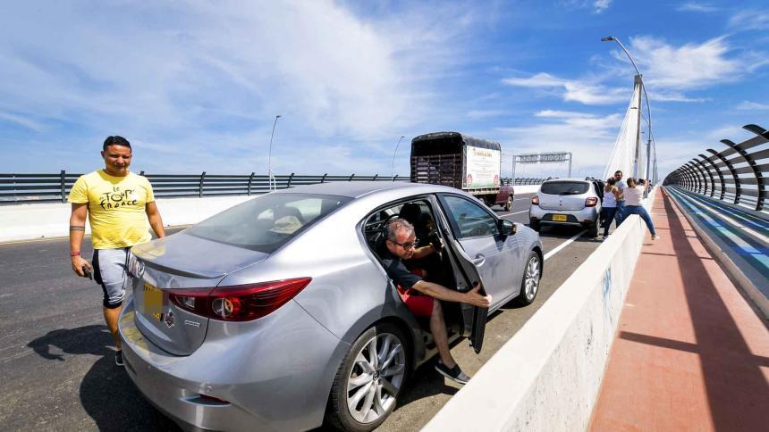 Personas estacionan en uno de los carriles  del puente y se bajan de los carros para tomarse fotografías.