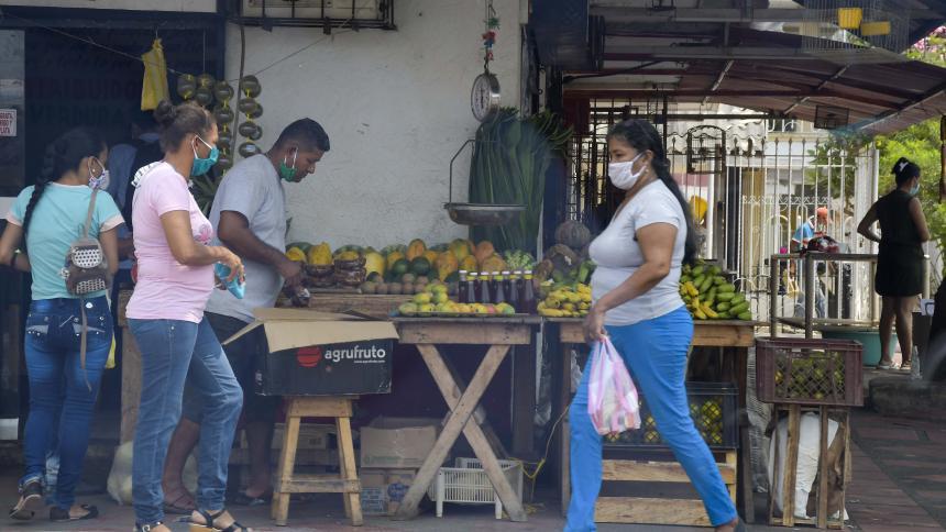 Compradores en un puesto callejero de frutas.