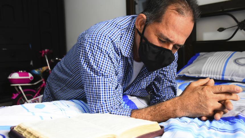 John Fredy  Torres (56 años) realiza una oración en su habitación.
