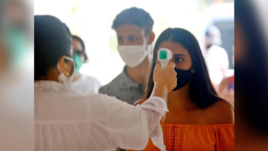 Una trabajadora de la salud haciendo medición de temperatura con un termómetro infrarrojo.