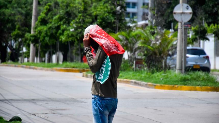Un hombre se cubre el rostro por el fuerte sol de la ciudad.