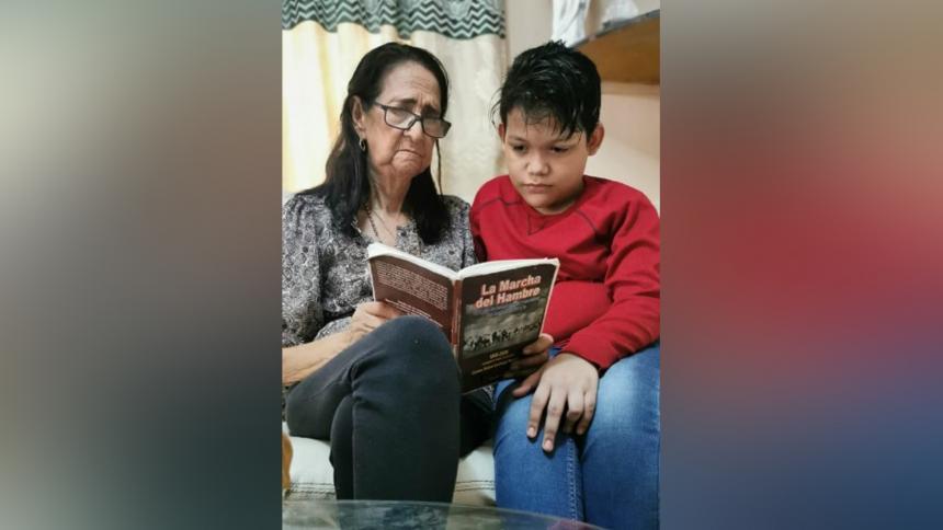 Isbelia Quinto de Fernández lee la Marcha del Hambre, del fallecido Rafael Hernández, a su nieto Carlos Andrés Arias Fernández.