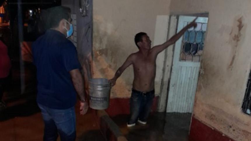 Un hombre señala los daños que el aguacero causó a su vivienda.