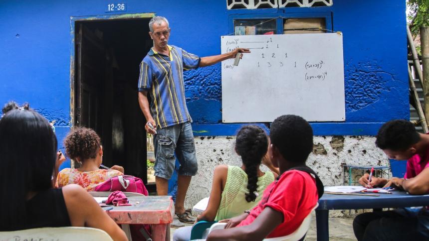 El profesor Raúl Ferrigno dicta clases a un grupo de niños y jóvenes en una calle del corregimiento de Orihueca, municipio Zona Bananera en el Magdalena.