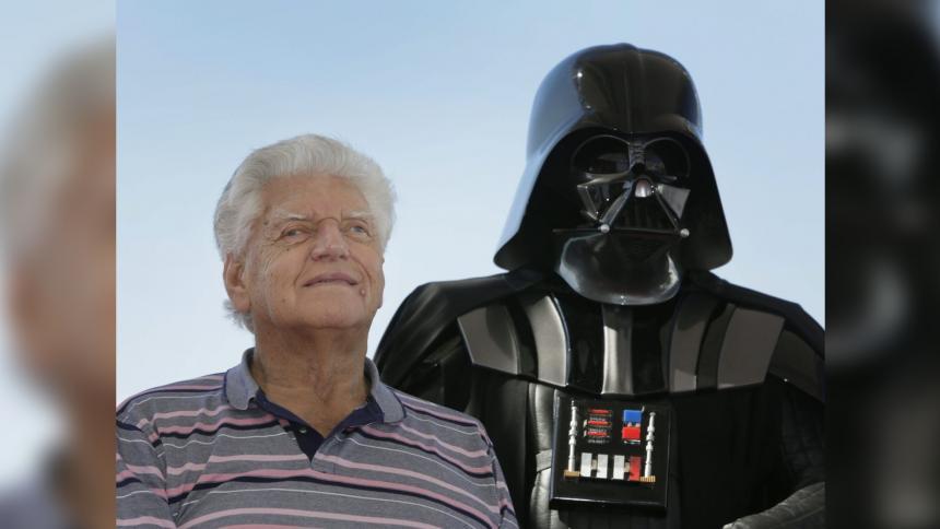 Dave Prowse posando junto a un traje del icónico antagonista de Star Wars, Darth Vader.