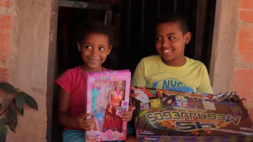 Dos niños del corregimiento de Tomarrazón, en Riohacha, sonríen luego de recibir sus juguetes de manos de la gestora social Belines Fuentes.