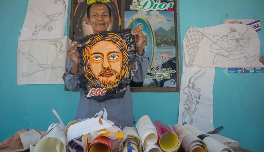 Roberto 'Roc' Orellano posando con el rostro polarizado de Jesucristo terminado en la oficina de dibujo en su casa.