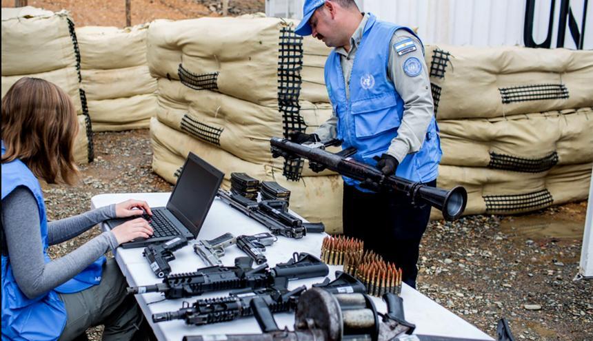 Dos funcionarios de la ONU supervisan las armas entregadas por el grupo guerrillero.