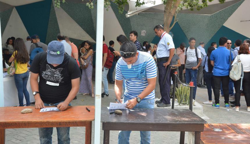 Dos estudiantes ejercen su derecho al voto mientras los demás hacen la fila.