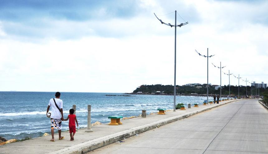 Un hombre y un niño caminan juntos por el Malecón de Puerto Colombia.
