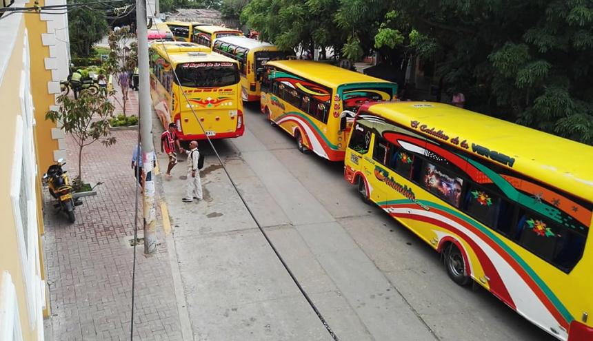 Vehículos parqueados alrededor de la plaza central.
