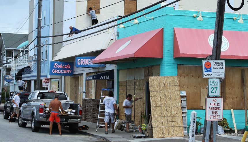 Trabajadores colocan tablas para proteger las vitrinas de algunas tiendas.
