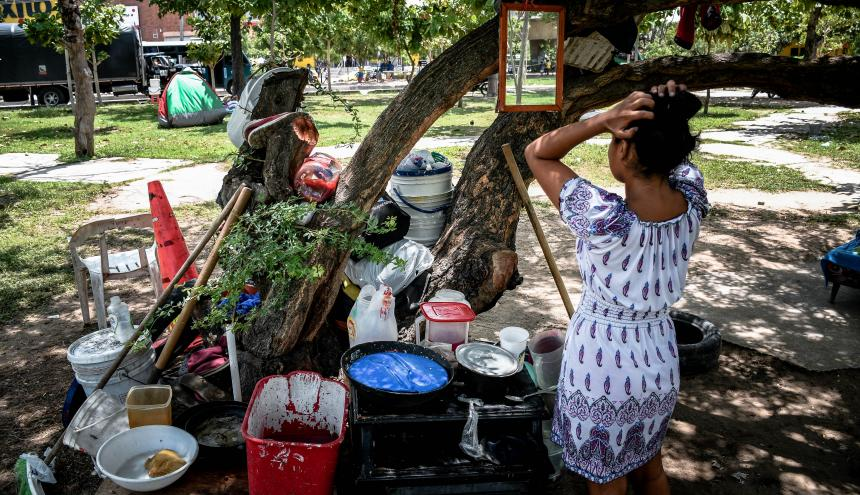 Una de las mujeres que se tomó la oreja del puente se observa en el espejo que está colgado en el árbol.