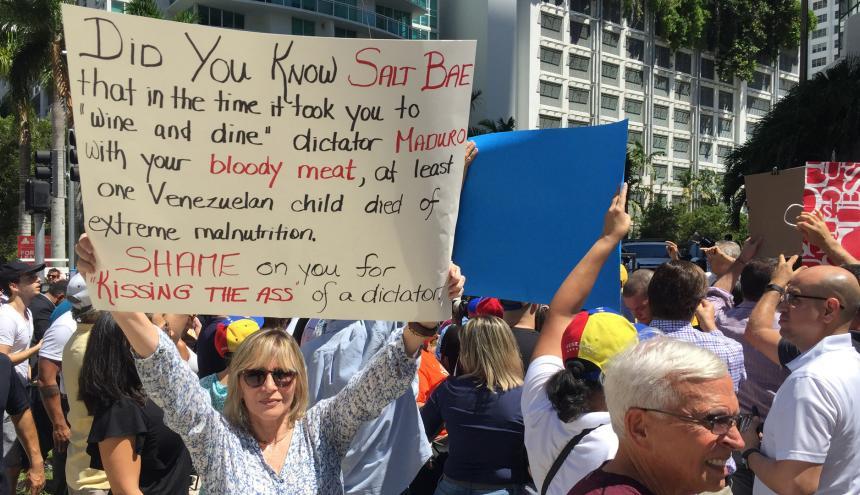 Una mujer carga un cartel donde muestra su descontento con el chef Salt Bae.