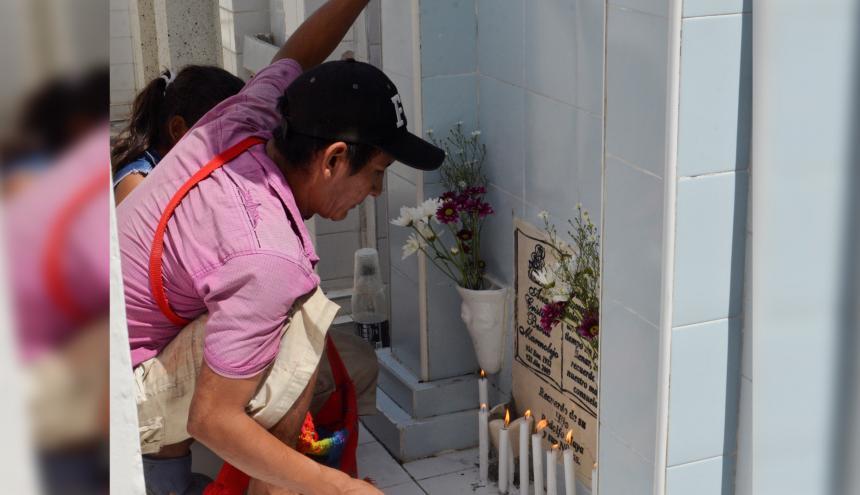 Durante la fiesta de los difuntos, familiares encienden velas y proclaman rezos en las tumbas.