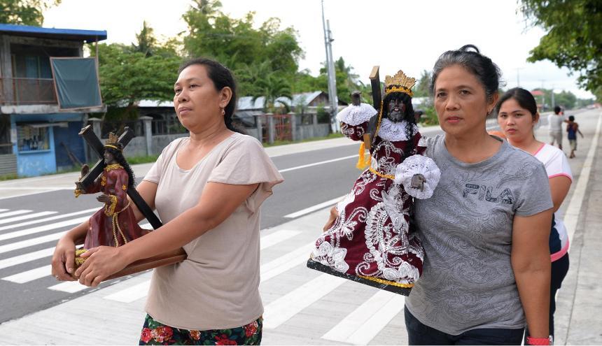Elsie Indic (izquierda), una sobreviviente del tifón Haiyan, marchando durante una procesión religiosa en Tolosa en la isla filipina oriental de Leyte.