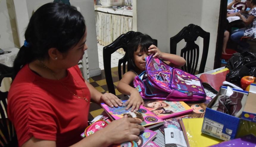 Claudia Echeverría, junto a su hija, desempaca los primeros útiles escolares adquiridos antes de la primera quincena de enero.