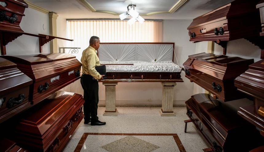 Un trabajador de una funeraria en Barranquilla revisa uno de los ataúdes que están exhibidos para su venta.