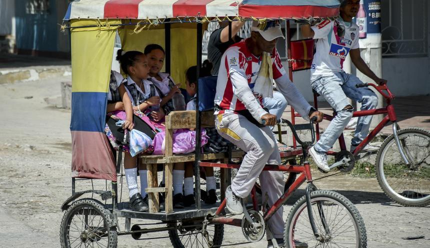Hasta cuatro niños por trayecto transportan los bicitaxistas hacia los colegios en el sur de Barranquilla.