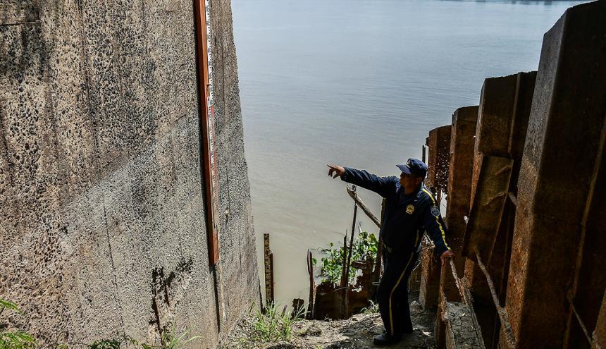 Un vigilante señala el metro con que se miden los distintos niveles del río.