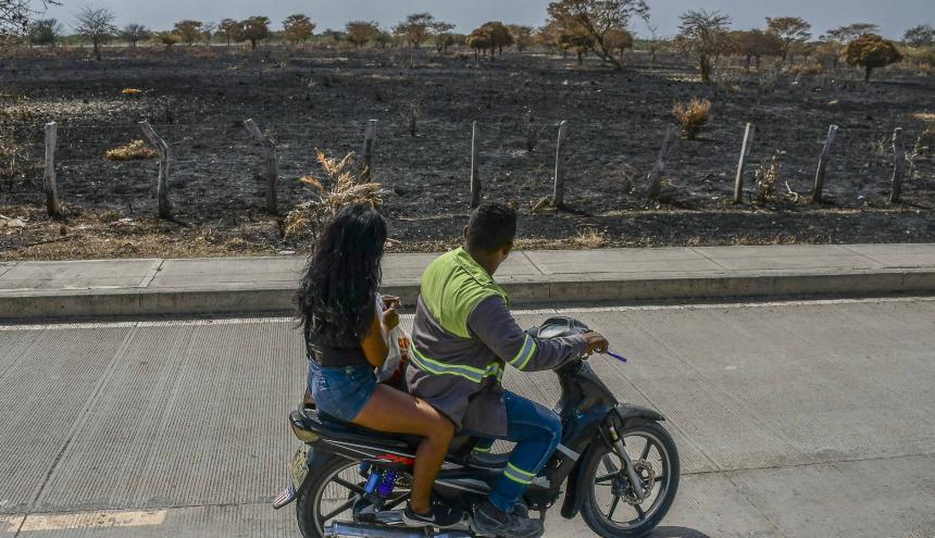 Motorizado y pasajero observan un área quemada en el municipio de Ponedera.